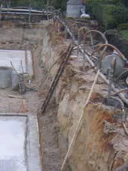 Baugrube mit fertiger Sohlplatte und geschlossener Wasserhaltung.