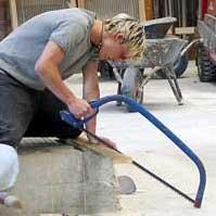 Ein Schüler schneidet mit der Bügelsäge ein Brett auf Länge.