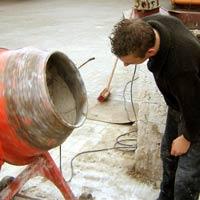 Das Bild zeigt einen Schüler beim Herstellen von Mauermörtel mit dem Freifallmischer.