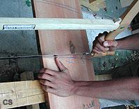 Ein Schüler setzt die Spannsäge an, um ein Brett abzusägen.