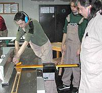 Ein Schüler hobelt eine schmale Leiste. Dabei wird er vom Ausbilder und von einem Mitschüler beobachtet.