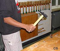 Ein Schüler arbeitet mit der Hobelbank. Im Fokus stehen ein Bankhaken und der Schüler, der zudem mit dem Hammer zum Schlag ausholt.