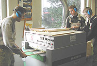 Drei Schüler arbeiten an einer Dickenhobelmaschine. Sie schieben Leisten in die Maschine bzw. nehmen sie ab.