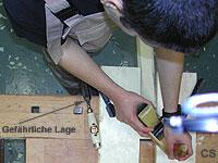 Ein Schüler bearbeitet mit dem Hobel eine Brettkante. Der Vorgang ist von oben fotografiert.