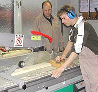 Ein Schüler arbeitet an einer Formatkreissäge. Beim Brettzuschnitt arbeitet er mit einer Zuführlade. Ein Ausbilder beobachtet ihn dabei.