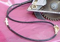 Auf der Abbildung ist eine Handkreissäge mit einem defekten Kabel zu sehen.
