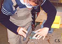 Ein Schüler ist am Glas schneiden. Dabei benutzt er ein entsprechendes Lineal und ein Werkzeug zum Ritzen des Glases.