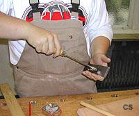 Ein Schüler stellt das Messer eines Hobels mithilfe eines Schraubendrehers ein.