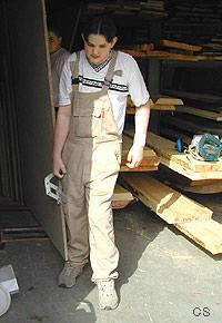 Auf diesem Bild ist ein Schüler zu sehen, der mit Hilfe eines Tragegriffes eine Spanplatte aus dem Lager herausträgt.