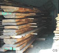 Hier ist ein Holzstapel mit eingeschittenen Brettern zu sehen. Die Bretter sind unsortiert und sind mit unterschiedlichen Lagerleisten - bzw. Hölzern gestapelt.
