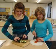 In diesem Bild sind zwei Schülerinnen beim Gemüseschneiden zu sehen.