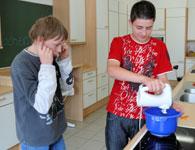Auf diesem Bild sieht man einen Schüler der mit dem Handmixer arbeitet. Ein anderer hält sich die Ohren zu.