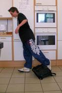 Ein Schüler stolpert über eine herumliegende Schultasche.