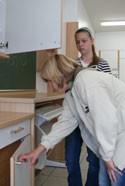 Hier ist eine Schülerin zu sehen, die sich zu einem Unterschrank herunterbeugt. Dabei übersieht sie, dass eine Oberschranktür offensteht.