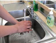 Auf diesem Bild ist zu sehen, wie sich jemand die Hände an einer Spüle wäscht.