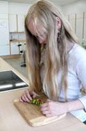 Hier schneidet eine Schülerin mit sehr langen, offenen Haaren GEmüse zu.