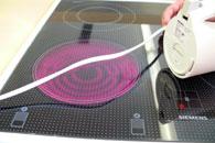 Auf diesem Bild ist zu sehen, wie das Kabel eines Wasserkochers über eine heiße Herdplatte gezogen wird.
