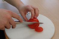 """Auf diesem Bild ist zu sehen, wie Gemüse mit dem """"Krallengriff"""" geschnitten wird."""