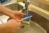 Auf diesem Bild ist zu sehen, wie ein Messer unter dem laufendem Wasserhahn gereinigt wird.