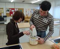 Hier sind zwei Schüler beim Rühren von Teig zu sehen. Während der Rührer sich noch dreht, möchte ein Schüler schon mit dem Finger den Teig probieren.