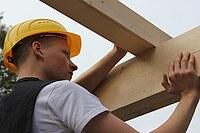 Das Bild zeigt einen Schüler, der ein Balken auf einem Rähmholz ausrichtet.