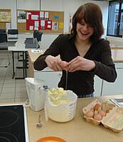 Hier ist eine Schülerin zu sehen die Eier in einer Rührschale aufschlägt.
