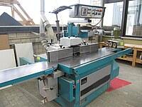 Das Bild zeigt eine Tischfräse zur Holzbearbeitung mit diversen Anbauteilen.