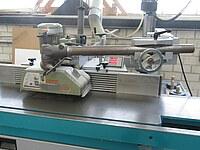 Hier ist eine moderne, manuelle Fräse zur Holzbearbeitung zu sehen. Zudem ist ein Vorschubgerät angebaut.