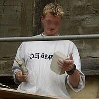 Das Bild zeigt einen Schüler, wie er einen Stein mit einem Maurerhammer bearbeitet.