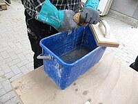 Hier ist zu sehen, wie ein Schwamm mit den Händen ausgewrungen wird. Dabei trägt die Person wasserdichte Handschuhe.