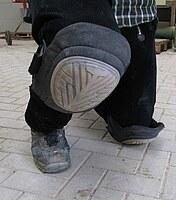 Dieses Bild zeigt eine kniehende Person, die Knieschutzpolster trägt.