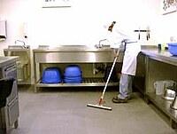 Ein Mitarbeiter bei der Bodenreinigung einer Großküche.