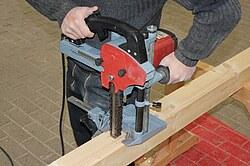 Das Bild zeigt, wie ein Zapfenloch mit einem Kettenstemmer ausbearbeitet wird.