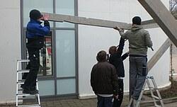Das Bild zeigt Schüler beim Richten einer Holzkonstruktion