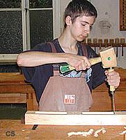 Ein Schüler bearbeitet ein Werkstück mit Klopfjholz und Stecheisen.