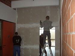 Dieses Bild zeigt, wie Schüler die gespachtelten Flächen einer Gipskartonwand abschleifen.