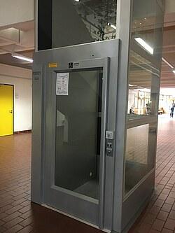Das Bild zeigt einen Aufzug moderner Bauweise, der nachträglich in ein Gebäude eingebaut wurde.