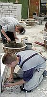 Schüler setzen Wandfliesen im Dickbett an.