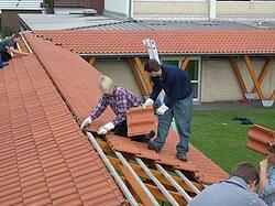 Das Bild zeigt Schüler, wie sie Dachziegel auf einer Dachlattung verlegen