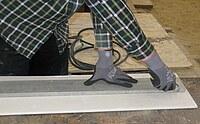Hier ist dargestellt, wie eine Gipskartonplatte geschnitten wird.