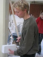 Das Bild zeigt einen Schüler, der einen KS- Stein mit einem Maurerhammer zurichtet.