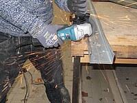 Hier wird ein U- Profil aus Metall mit dem Winkelschleifer zugeschnitten.