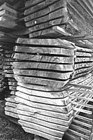 Auf dem Bild sind mehrere, frisch eingeschnittene Holzstapel zu sehen. Die Bretter sind stammweise aufeinandergelegt.