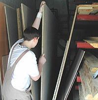 Hier ist ein Schüler zu sehen, der eine Spanplatte aus den senkrecht stehenden Platten auswählt.