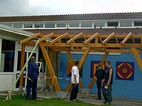 Das Bild zeigt eine Gruppe von Schülern beim Abschwerten einer Holzkonstruktion.