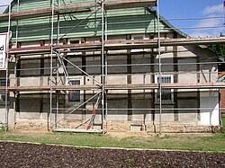 Bas Bild zeigt ein errichtetes Fassadengerüst vor einem Fachwerkhaus