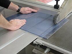Hier ist zu sehen, wie eine Plexi- Glasscheibe an einer Formatkreissäge zugeschnitten wird