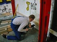 Ein Schüler bohrt mit dem Bohrhammer durch ein Brett in die Wand hinein, um danach das Brett mit einem Nageldübel zu befestigen.