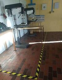 Die Abbildung zeigt einen abgegrenzten Arbeitsbereich um zwei Ständerbohrmaschinen herum.