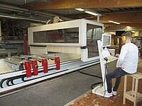 Hier ist ein Bearbeitungszentrum zu sehen. Ein Mitarbeiter grogrammiert die Maschine. Des weiteren ist die Einhausung des Maschinenkopfes und ein Teil des Spanntisches zu sehen.